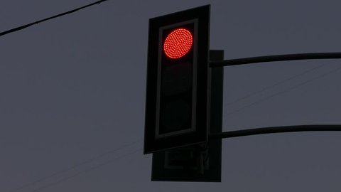 Ungraded: Automobile traffic lights over the road change the light from red to yellow, and then to green at evening. Source: Lumix DMC, ungraded H.264 from camera without re-encoding. (av39953u)