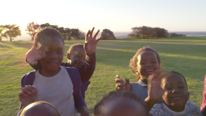Elementary school kids waving to camera outdoors, close up