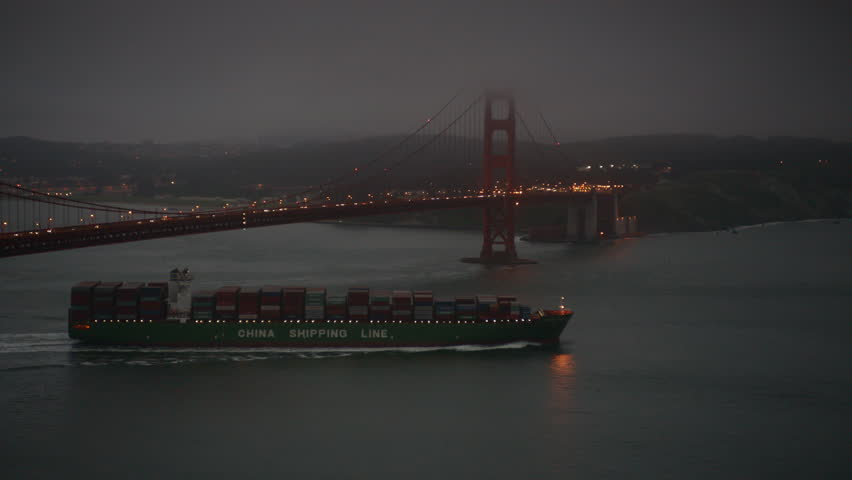 SAN FRANCISCO, CA - circa 2016: Super freighter cargo ship with containers on deck going under Golden Gate Bridge California at night. 4K