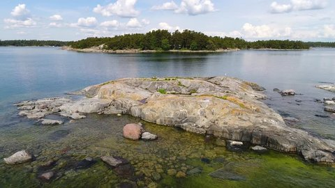 4K aerial close up: Drone flying over rocky islet with bird and above water to shore of island with cabin and boat and rising over pine tree forest. Inkoo archipelago. Finland. Scandinavia. 2017