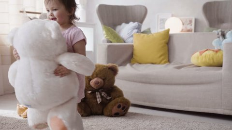 two little happy girl kids play actively with plush toys and teddy bears, hugging them with love and dancing with fun, enjoying and laughing at home in room during sunny day