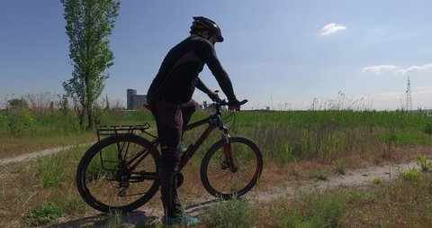 Camera from below: mature man in helmet on bicycle walk on dirt road among reeds of summer river landscape
