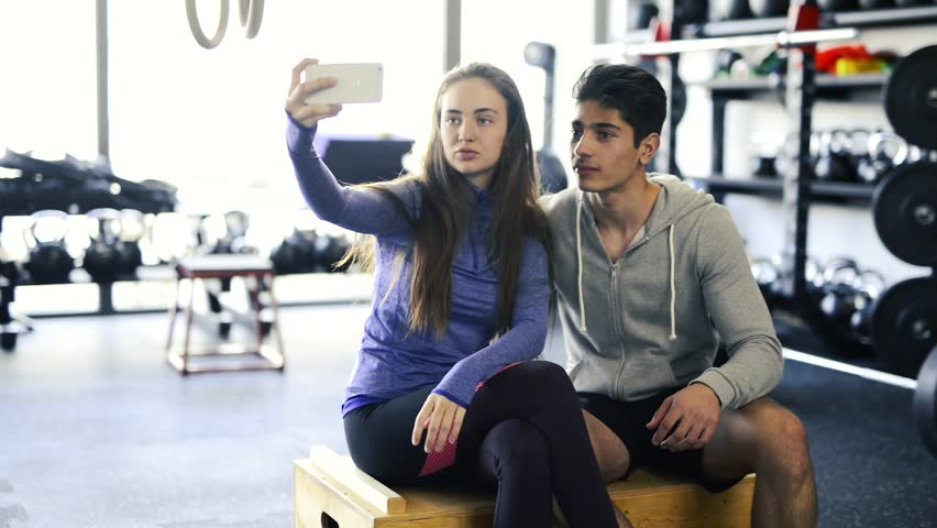 Fit couple in crossfit gym taking selfie with smartphone.   Shutterstock HD Video #28075243