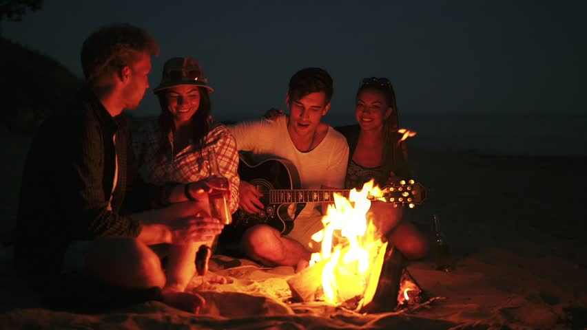 Picnic of young people with bonfire on the beach in the evening. Cheerful friends singing songs and playing guitar. Slowmotion shot | Shutterstock HD Video #28078153