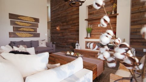 Modern Living Room Angle Reveal from Behind Plant. a large modern rustic industrial living room with a large reclaimed wood wall revealed from behind a plant