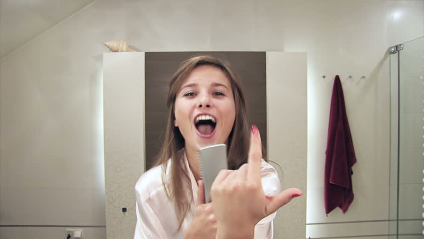 gorgeous blonde girl having fun in a bathroom singing Hit the Road Jack - no color grading (color corrected version available, file nr 4056895)