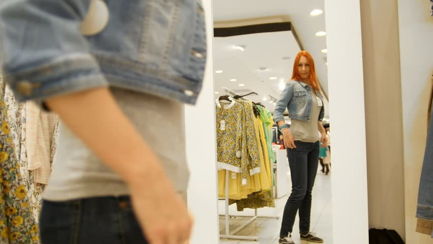 Pretty woman trying on jeans jacket in fitting room of store | Shutterstock HD Video #28099504