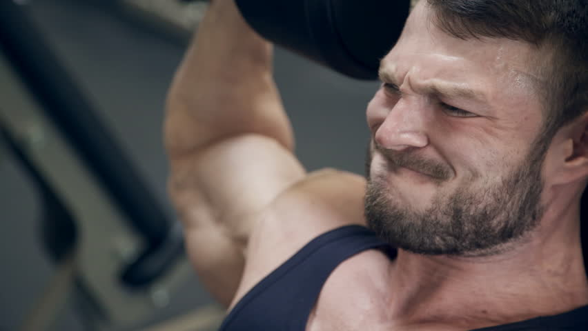 Strong man lifts heavy weights over head in gym. Young handsome brunette man in black sportswear, with bristles, sits in gymnasium, doing exercise using muscles of hands. Close-up view on face of