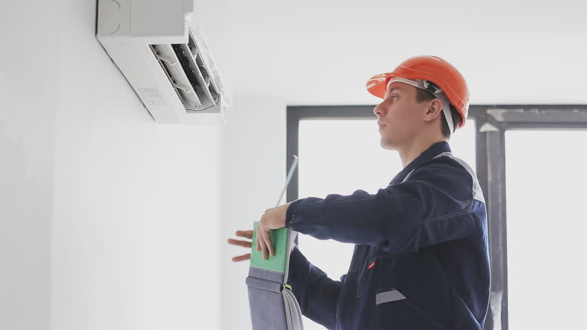 serviceman inspects and measures a air conditioning