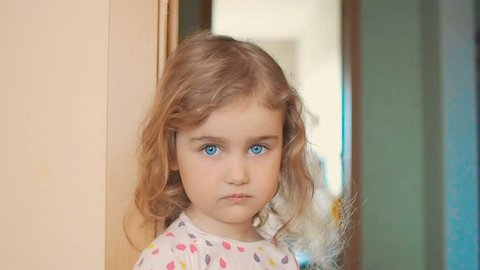 Little girl is blonde with blue eyes stands near the wall in the house. Child with regret looking at the camera,portrait of a sad girl.