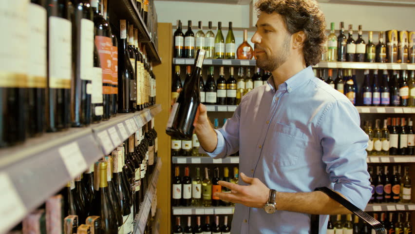 Young attractive man choosing the good bottle of wine in the supermarket and putting it to the basket.