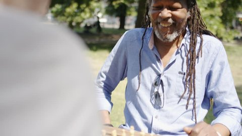 Jamaican man smiles as he plays a game of chess with an old friend in the park