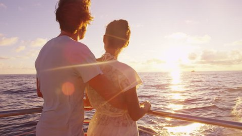 Cruise ship - Romantic couple enjoying sunset over the ocean on small cruise ship sailing on open sea. Woman and man in love on boat travel sailing during vacation.