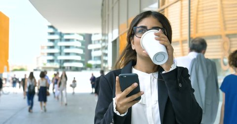 Portrait of a young beautiful business woman (student) in a suit, glasses, walking around the city, drinking coffee, talking on the phone. Concept: new business, communication, Arab, banker, manager.