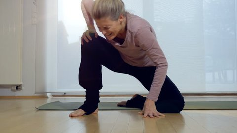 Woman cringing in pain after attempting to stand up following yoga exercise. Full length.
