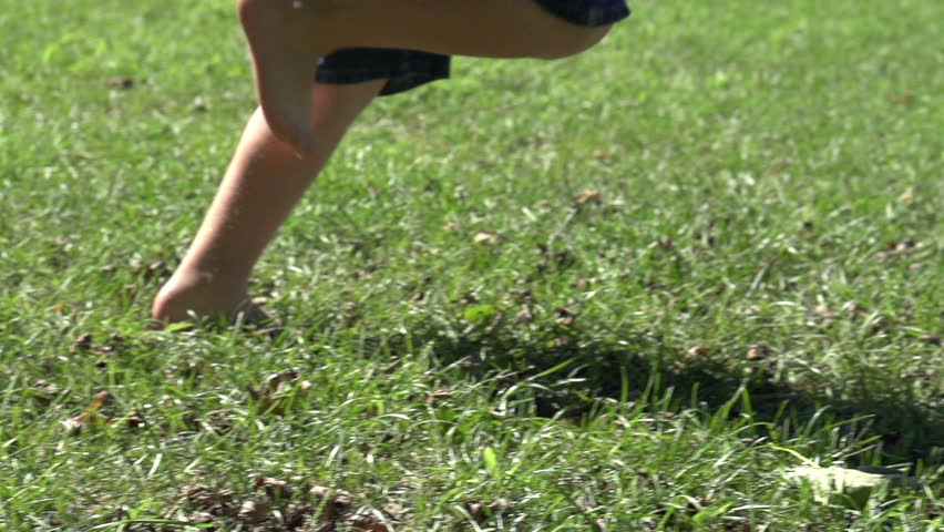 Boy running by in grass slow motion