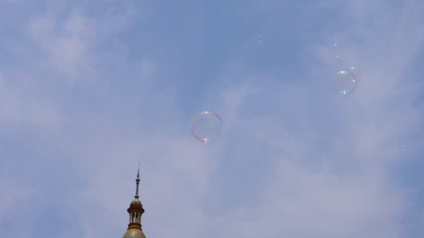 HD. Slow motion. Beautiful image of soap bubbles flying towards the sky. The pomps fly in the Plaza de España in Seville. In contact with the air, the spheres are exploited