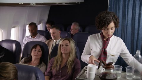 Flight attendant serving drinks to airliner passengers