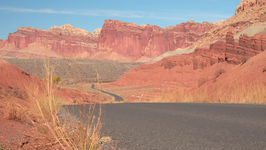 Empty road leading past eroded butte and mesa mountains in red rocky desert on summer day. Road going through Capitol Reef Park past rocky mountain formations in Utah desert landscape, United States