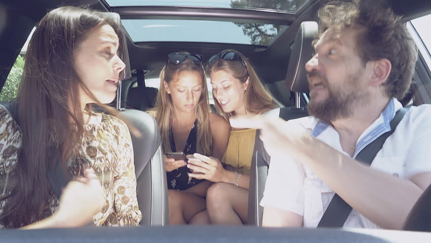 Father and mother fighting driving car while daughters in back seat laugh with cell phone flat