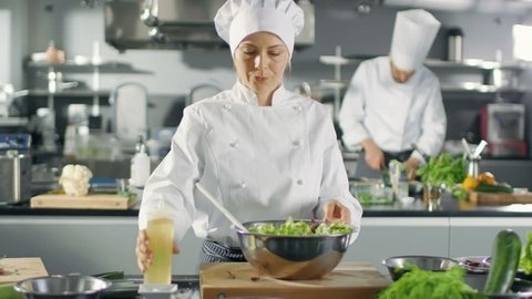 In a Famous Restaurant Female Cook Prepares Salad, ads Oil. She Works in a Big Modern Kitchen. Shot on RED EPIC-W 8K Helium Cinema Camera.