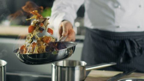 Professional Chef Cooks Flambe Style. He Prepares Dish in a Pan with Open Flames. He Works in a Modern Kitchen with Different Ingredients Lying Around.  Shot on RED EPIC-W 8K Helium Cinema Camera.