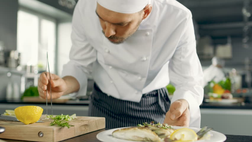 Famous Chef Decorates His Special Fish Dish with Some Greens. He Works in a Modern Kitchen.  Shot on RED EPIC-W 8K Helium Cinema Camera.