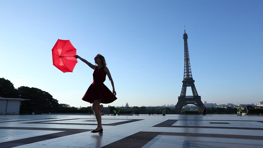 Slow motion of a happy cheerful girl dancing near Eiffel Tower with a red umbrella, Paris, France