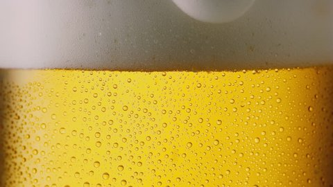 Foam sliding down of a beer glass with dew, 4k