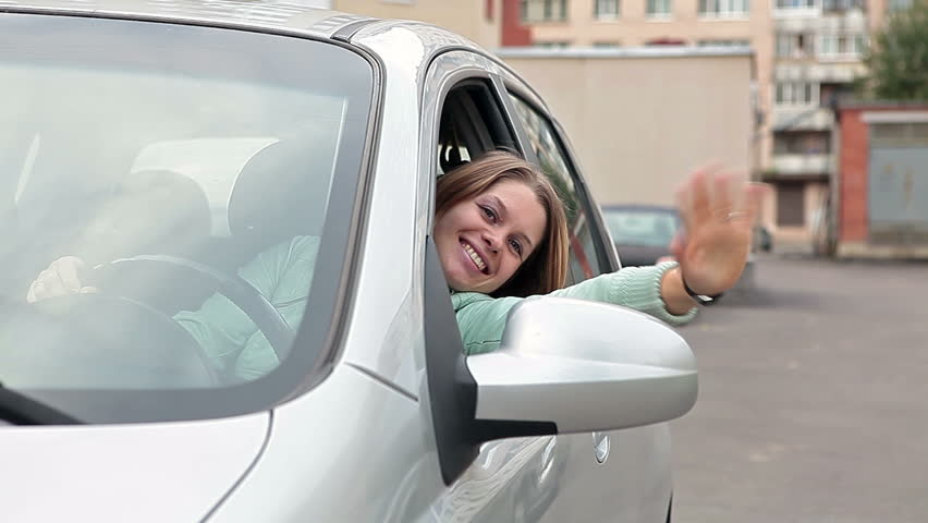Female driver sitting in own car and looking on camera from back window, smiling and waving