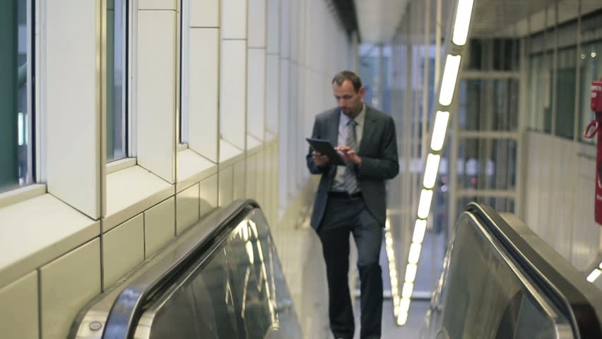 Businessman with tablet computer on escalator