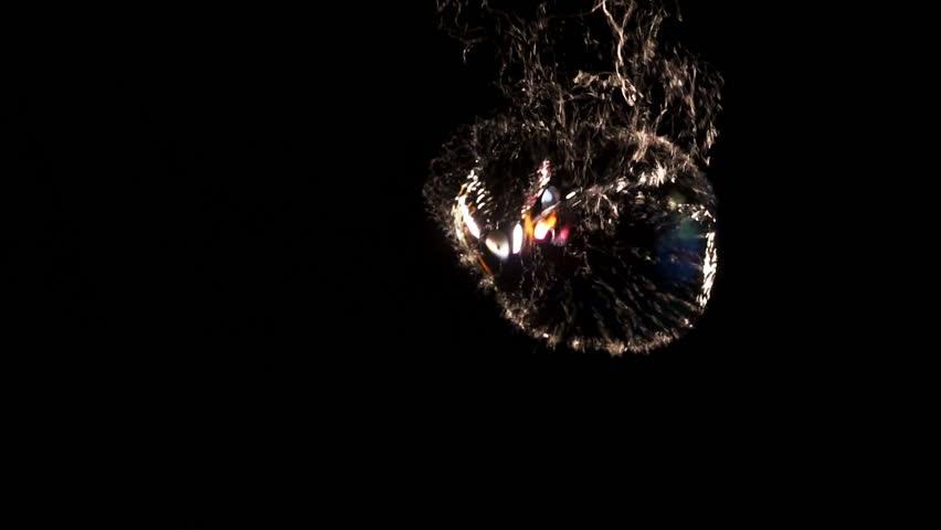 Bubble bursting in slow motion against black background