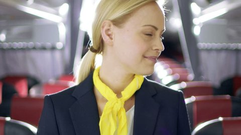 On a Plane Beautiful Blonde Stewardess/ Flight Attendant Smiles with Warm and Welcoming Smile. Airplane Looks New. Shot on RED EPIC-W 8K Helium Cinema Camera.