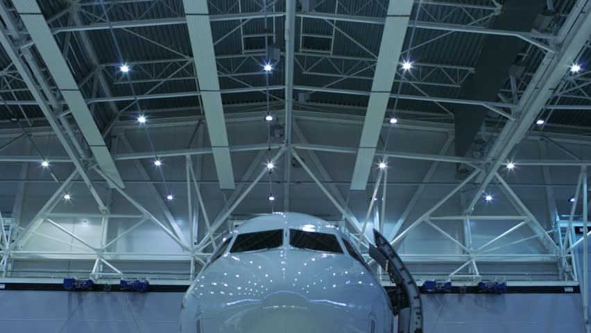 Up-Down Shot of a Brand New Airplane Standing in a Aircraft Maintenance Hangar. Plane's Door is Open and Ladder Stands Beside it. Shot on RED EPIC-W 8K Helium Cinema Camera.