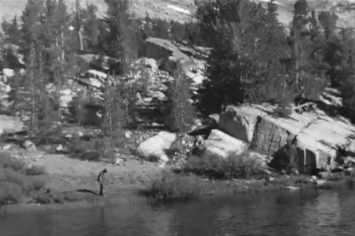 1960s: Kids play on the grass next to a lake in the Sierra mountains, trying to catch a frog, in home video footage from the 1960s by renowned environmentalist David Brower.