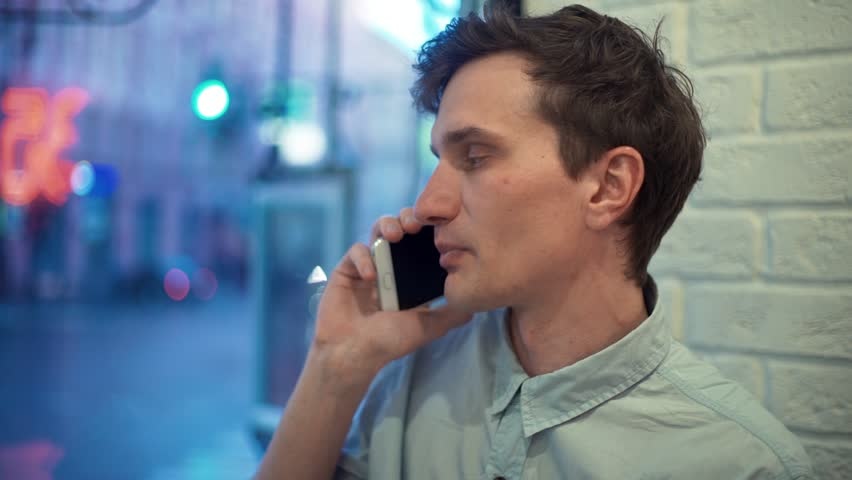 Happy young man in blue shirt talking on phone and celebrating success in cafe in evening. Freelancer working in cafe. Street traffic outside the window. | Shutterstock HD Video #28330537
