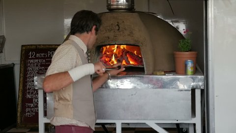 Italian Pizza Chef Cooking - June 2017. The Chef with the use of Pizza shovel Sliding and shuffling a fresh Pizza in a wood fired Pizza Oven