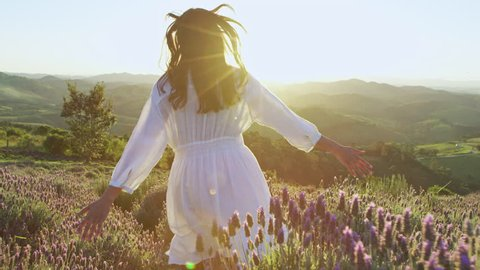Beautiful woman wearing white dress running through beautiful purple lavender field at sunset. Golden hour.