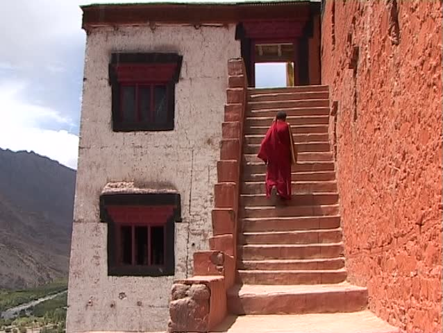 Monk is climbing up monastery entrance in Ladakh