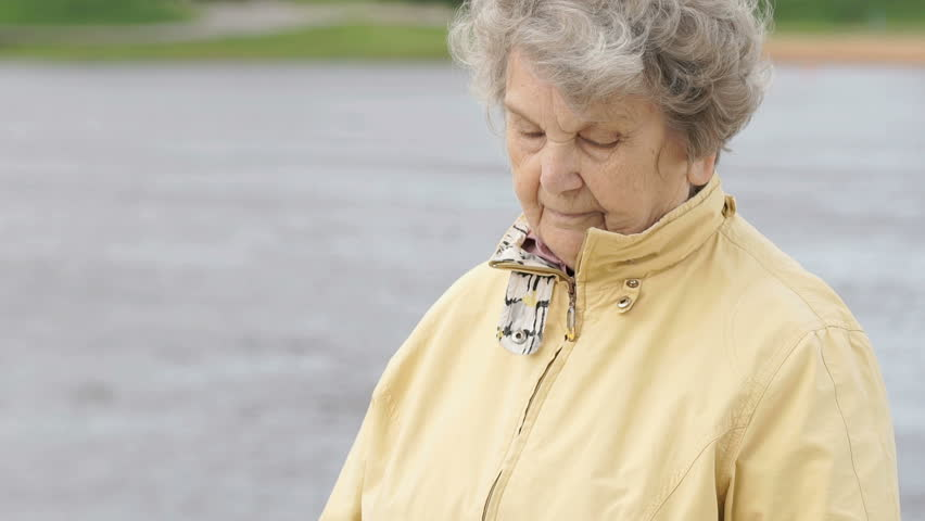 Black wristband. Outdoors, an old woman, aged 80s, dressed in a yellow jacket, looks at the results of physical activity using a wristband fitness tracker outdoors.
