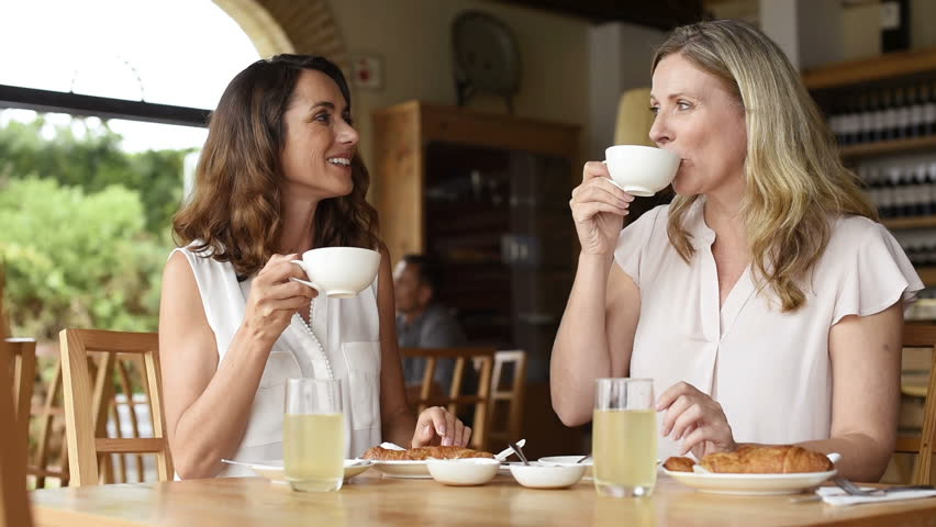 Two beautiful mature women holding cup of coffee and talking to each other in a cafeteria. Senior women in conversation while having breakfast. Happy middle aged friends meeting up for coffee.  | Shutterstock HD Video #28383643