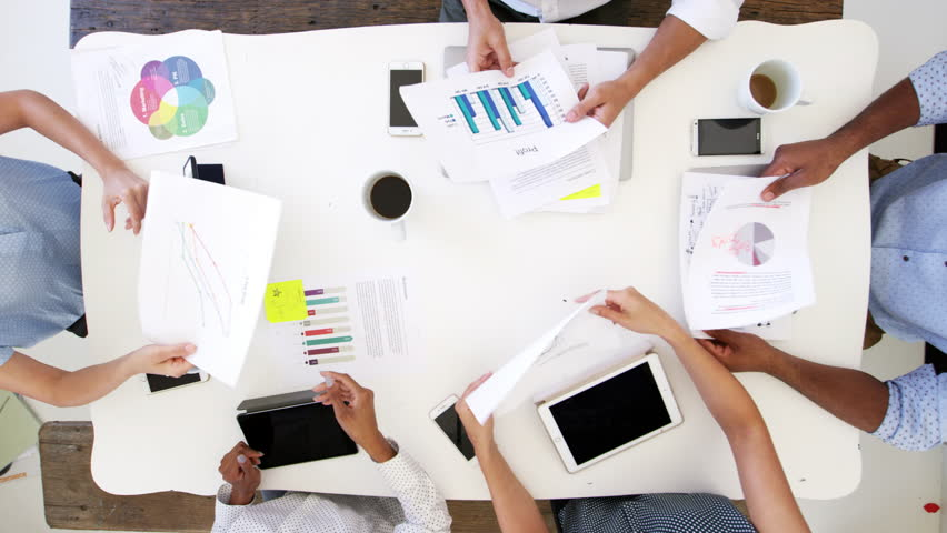 Business people at a desk passing documents, overhead shot | Shutterstock HD Video #28384888