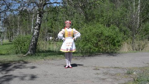 The girl in a national Russian (Belarusian) suit dances against the background of the Belarusian nature. Ethno style. Russian (Belarusian) folklore.