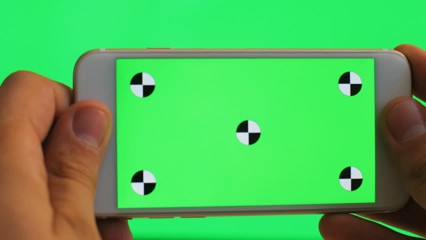Male hand holding white cell phone with green screen on green background. Tracking motion. Chroma Key. Horizontal. Very close up
