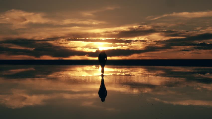 Silhouette of woman walking on incredible panorama of Uyuni salt flats at the golden sunset. Bolivia.