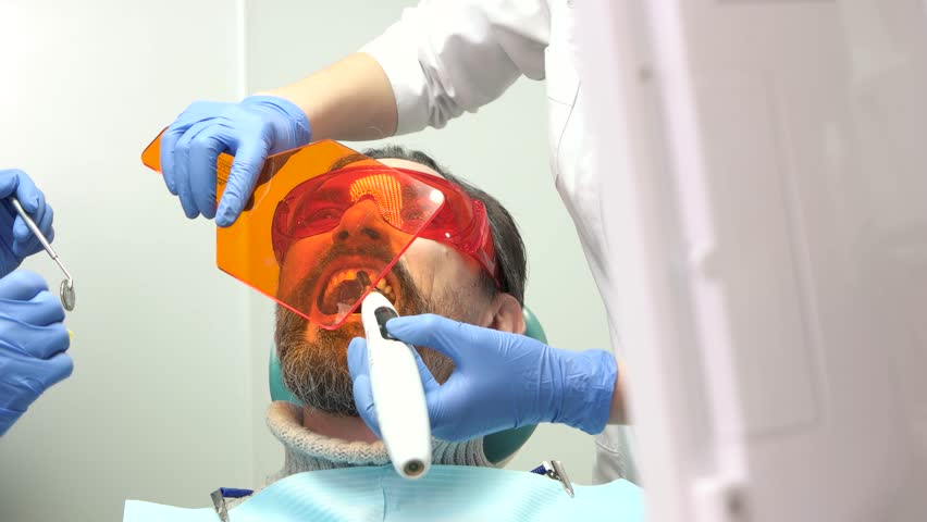 Two dentists at work. Stomatologist using UV light. Knowledge, skills and experience.   Shutterstock HD Video #28443823