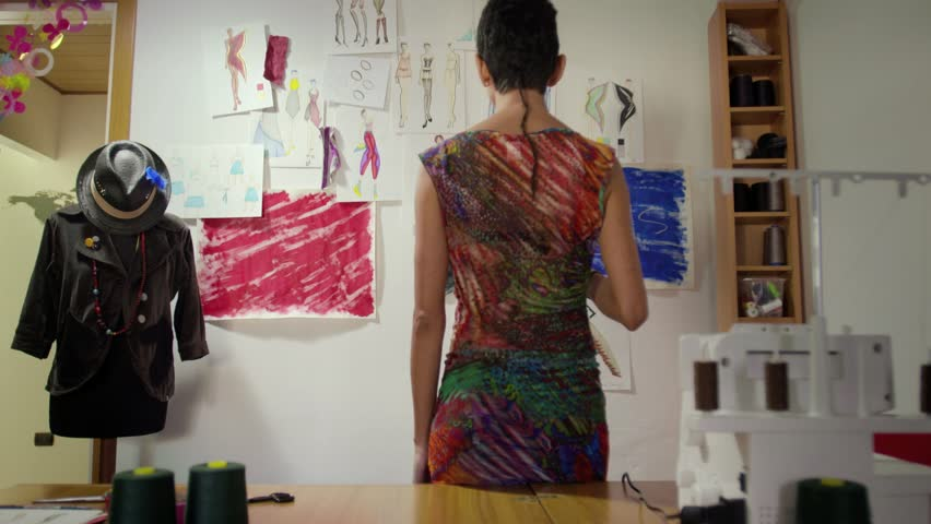 Hispanic woman at work as fashion designer and tailor, looking at sketches in atelier. Sequence