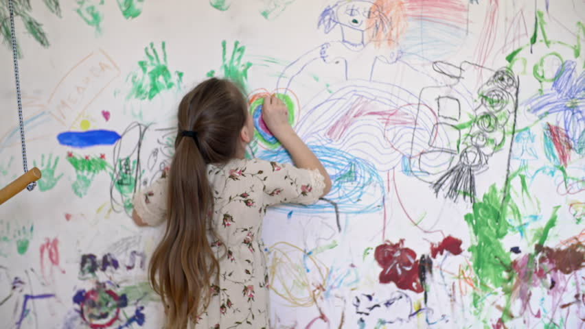 Medium shot with rear view of little girl in linen dress drawing colorful heart on wall of her room covered in doodles