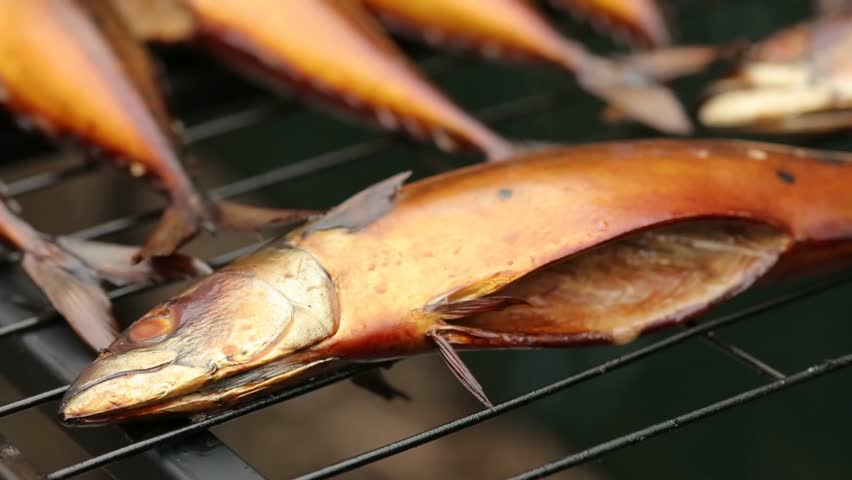 Mackerel hot smoked. A fish of golden color lies on the trellis. Carcasses of fish in smokehouse from which there is a light smoke | Shutterstock HD Video #28509763