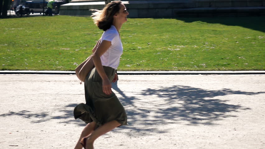 Late woman running in hurry through park in city, super slow motion 240fps
